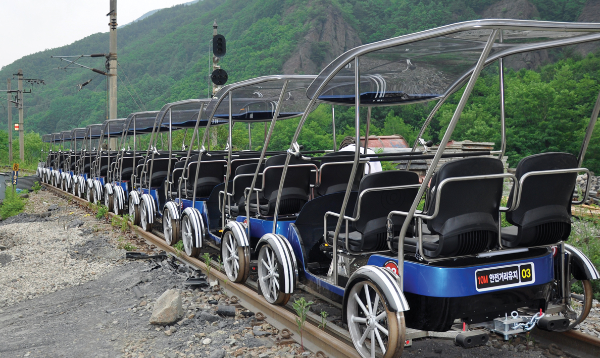 Funicular railway system, family rail bikes hauled up mountain by the train | South Korea